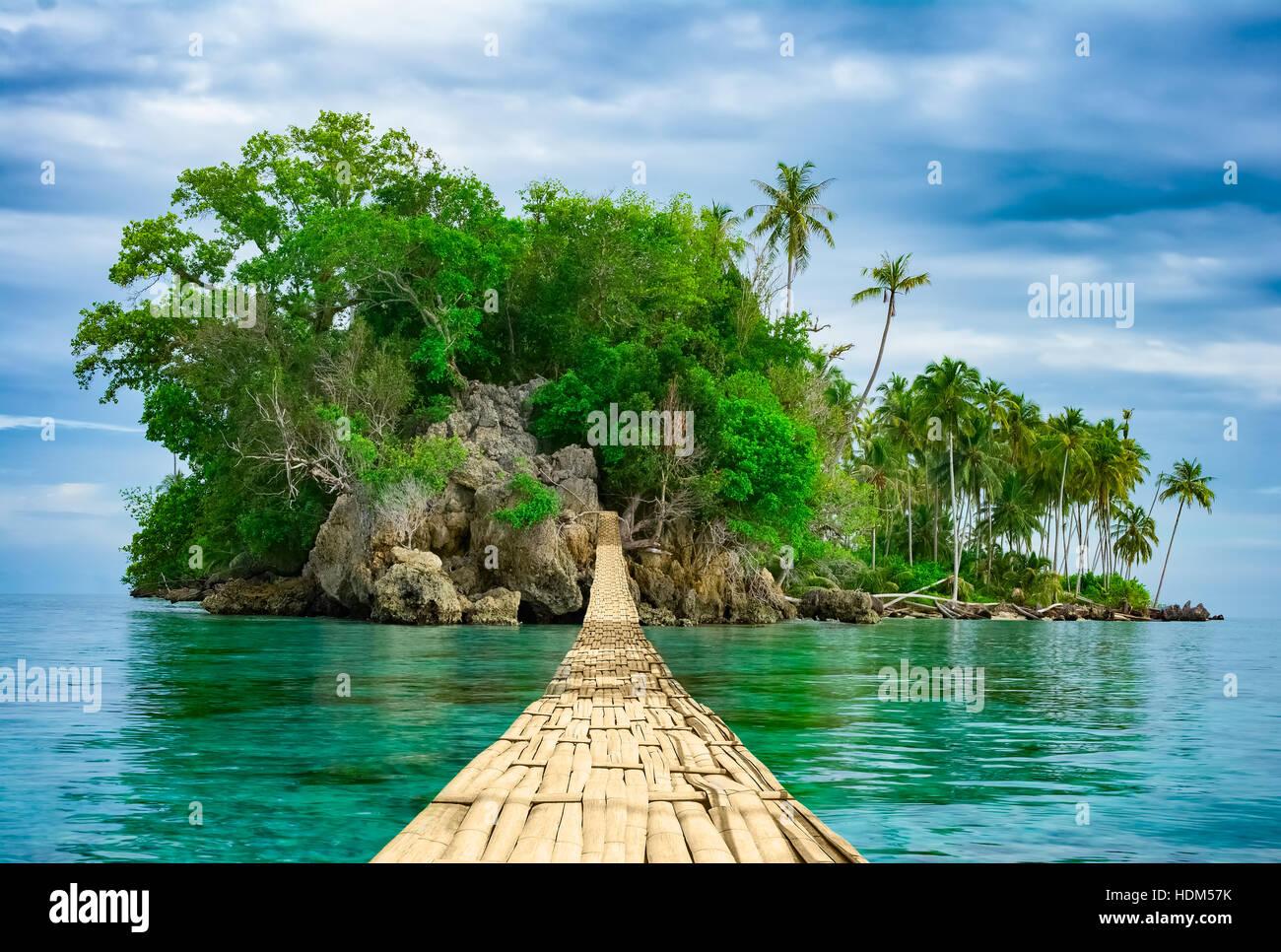 Bamboo pedestrian hanging bridge over sea to remote desert island. Beautiful tropical landscape. Travel lifestyle. Stock Photo