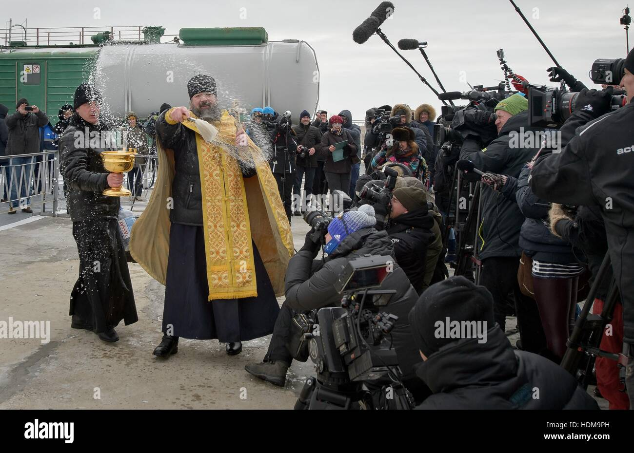 A Russian Orthodox Priest blesses members of the media after blessing the Soyuz MS-03 spacecraft rocket in preparation - Stock Image