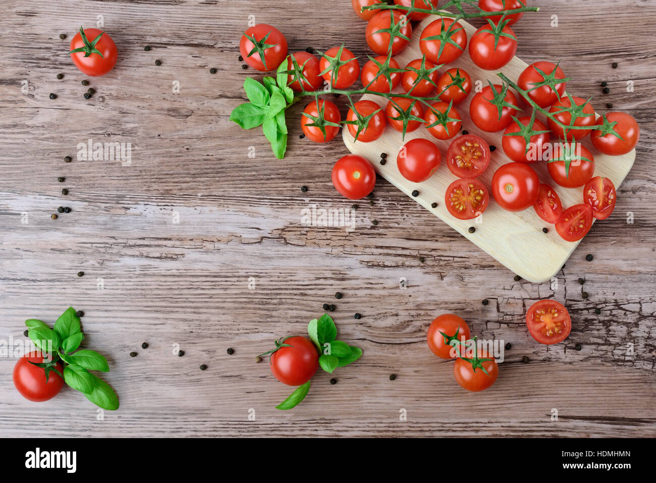 Tomatoes and pepper in groups with leaves of basil, on the brown wooden table. - Stock Image