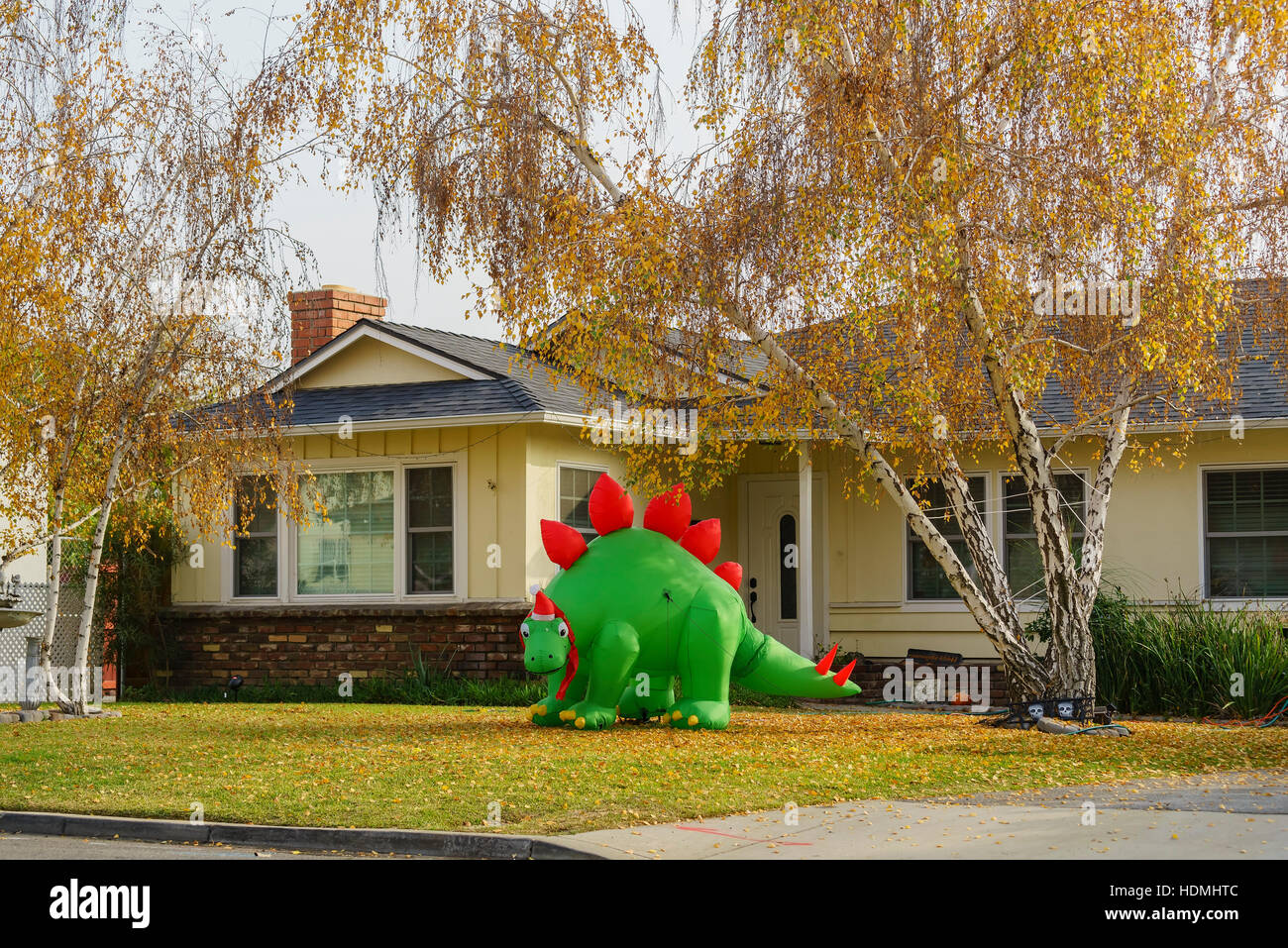 Temple City, DEC 12: Inflatable dinosaur christmas decoration and fall color in front of a house on DEC 12, 2016 - Stock Image