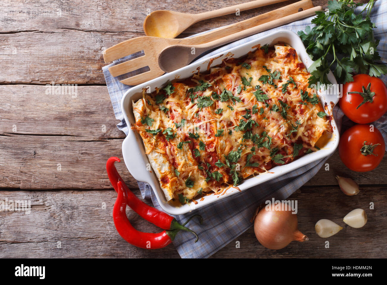 Mexican enchilada in a baking dish with the ingredients on the table. horizontal view from above Stock Photo