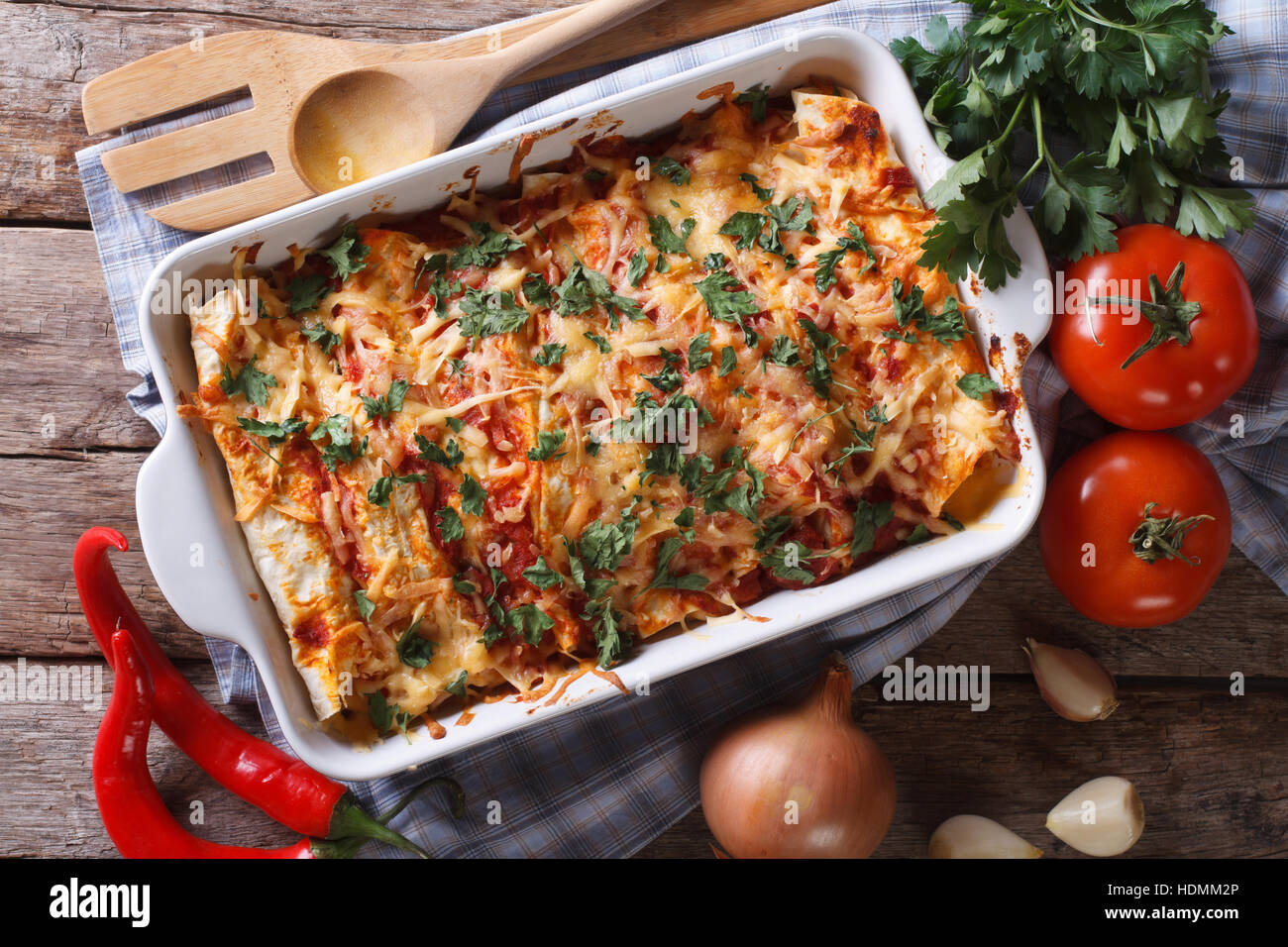 Mexican enchilada in a baking dish with the ingredients on the table close-up. horizontal view from above Stock Photo