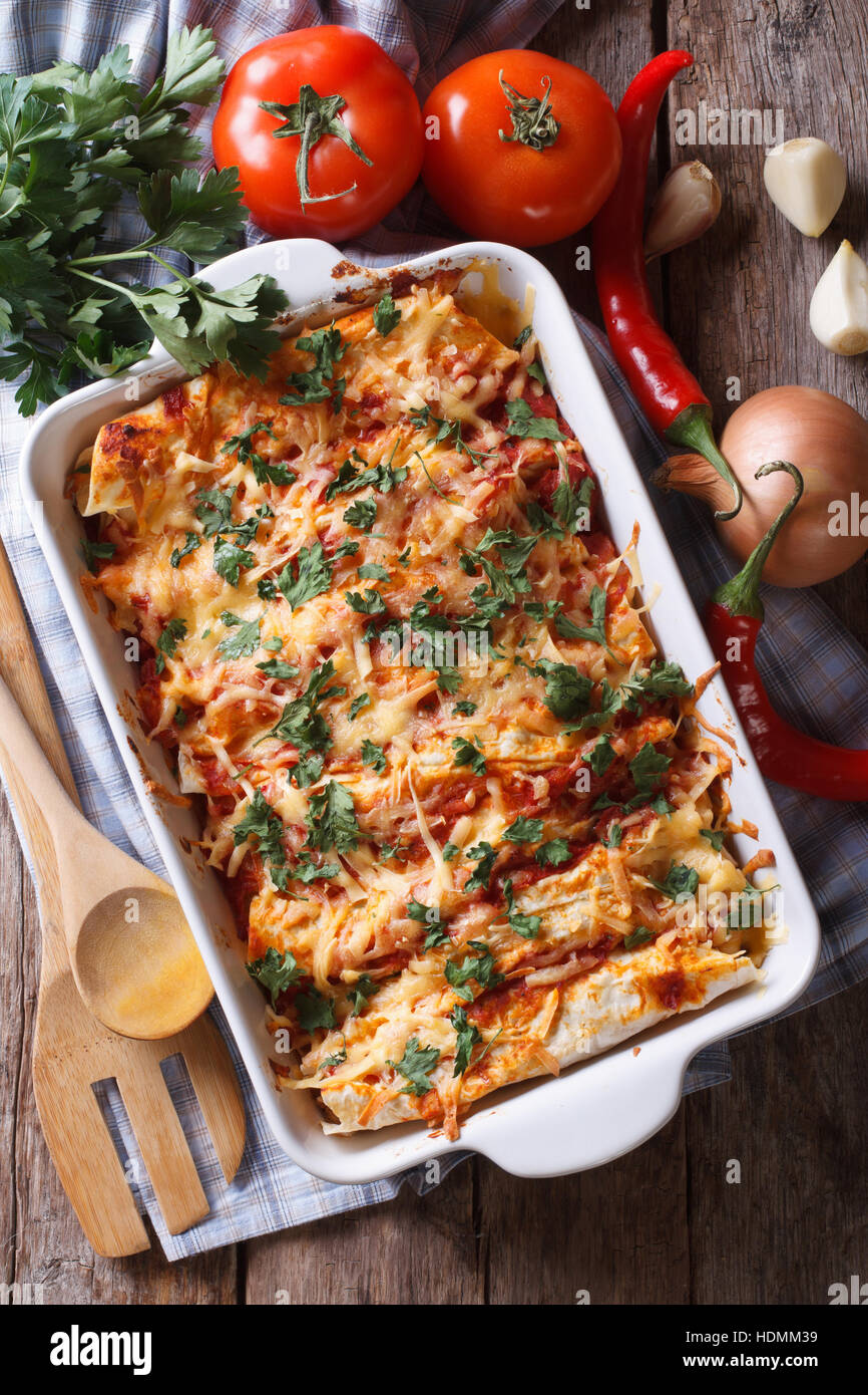 Mexican enchilada in a baking dish with the ingredients on the table. vertical view from above close-up Stock Photo