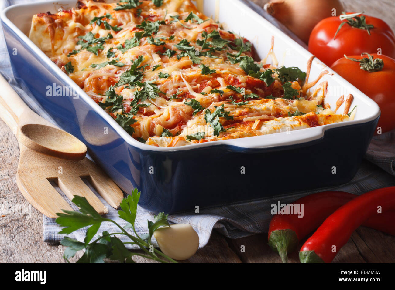 enchilada in baking dish closeup and ingredients on the table. horizontal Stock Photo