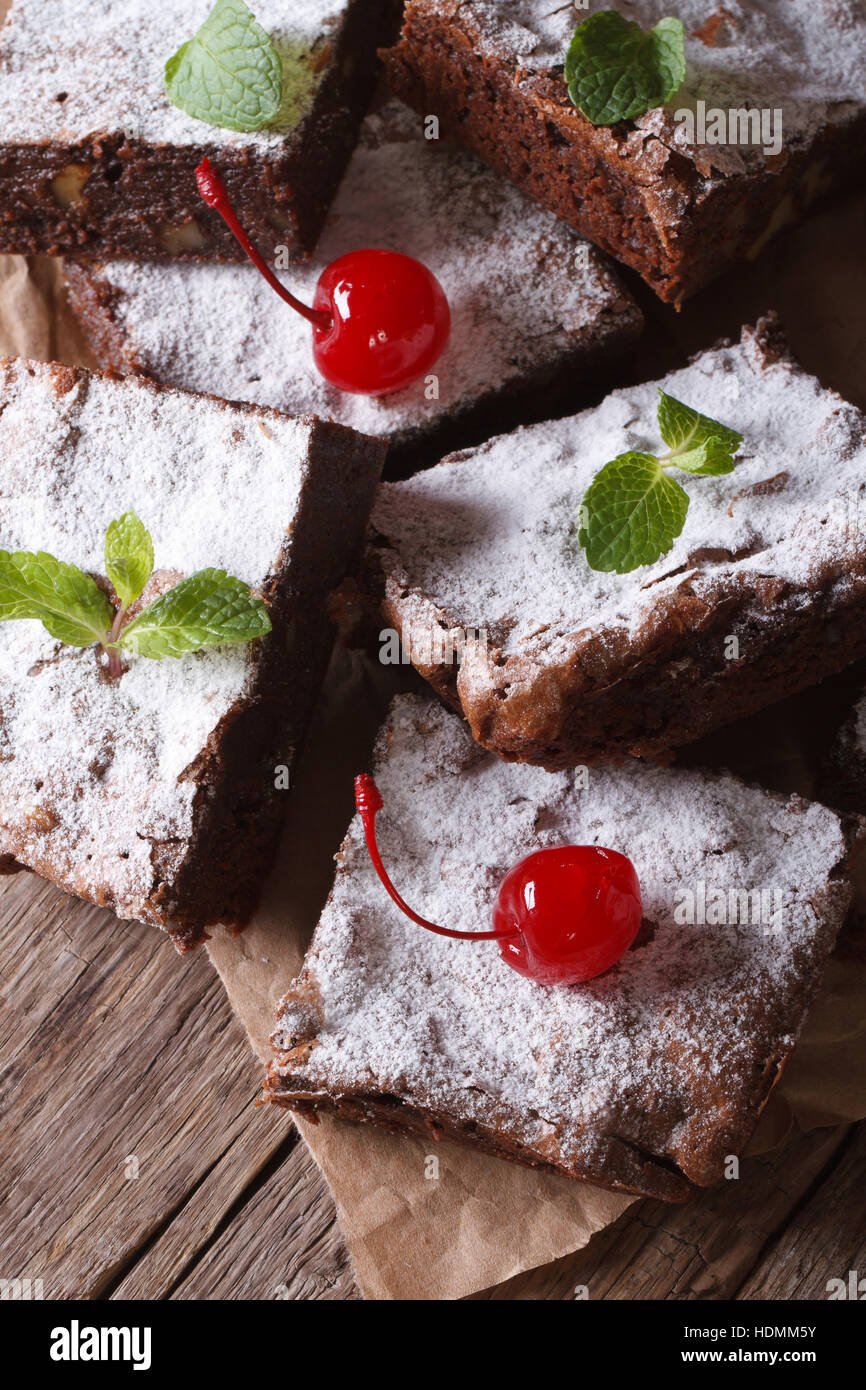 chocolate cake brownies with mint and cherry closeup on paper. vertical - Stock Image
