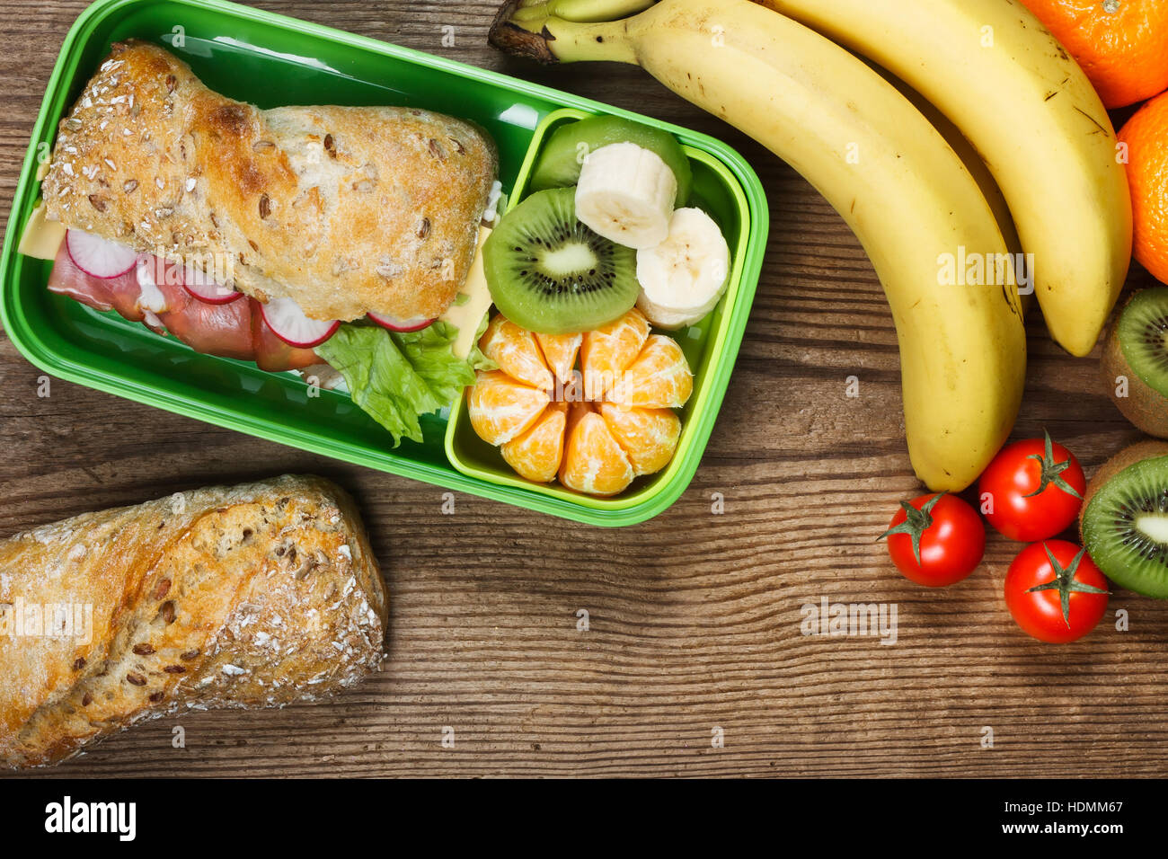 Lunchbox on wooden table. Ham sandwich and fruits in plastic box - Stock Image