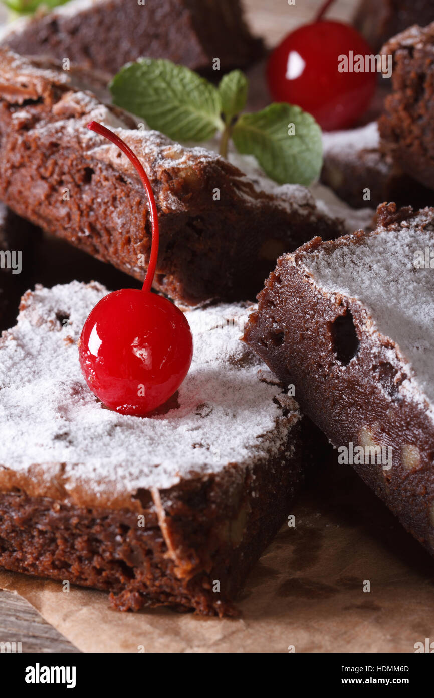 delicious chocolate cake brownies with nuts and cherries macro on paper. vertical - Stock Image