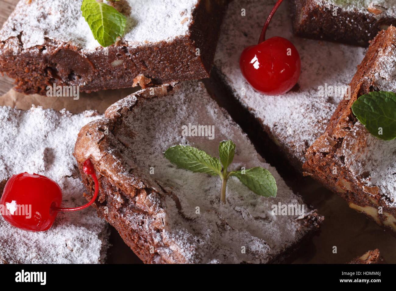 chocolate cake brownies with mint and cherries macro. horizontal - Stock Image