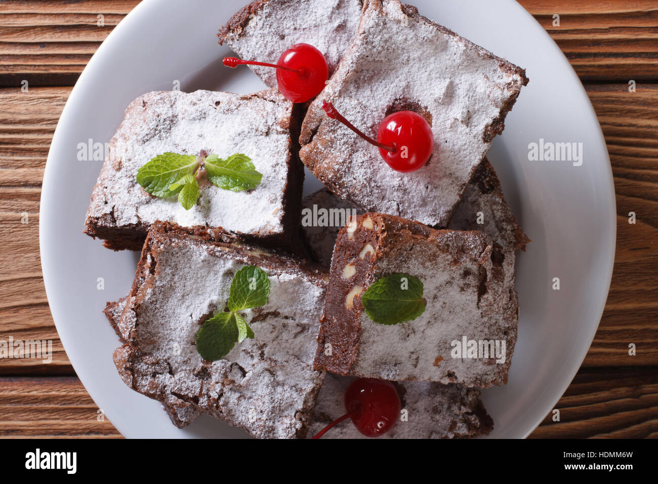 chocolate cake brownies with mint and cherries on a white plate. horizontal top view close-up - Stock Image