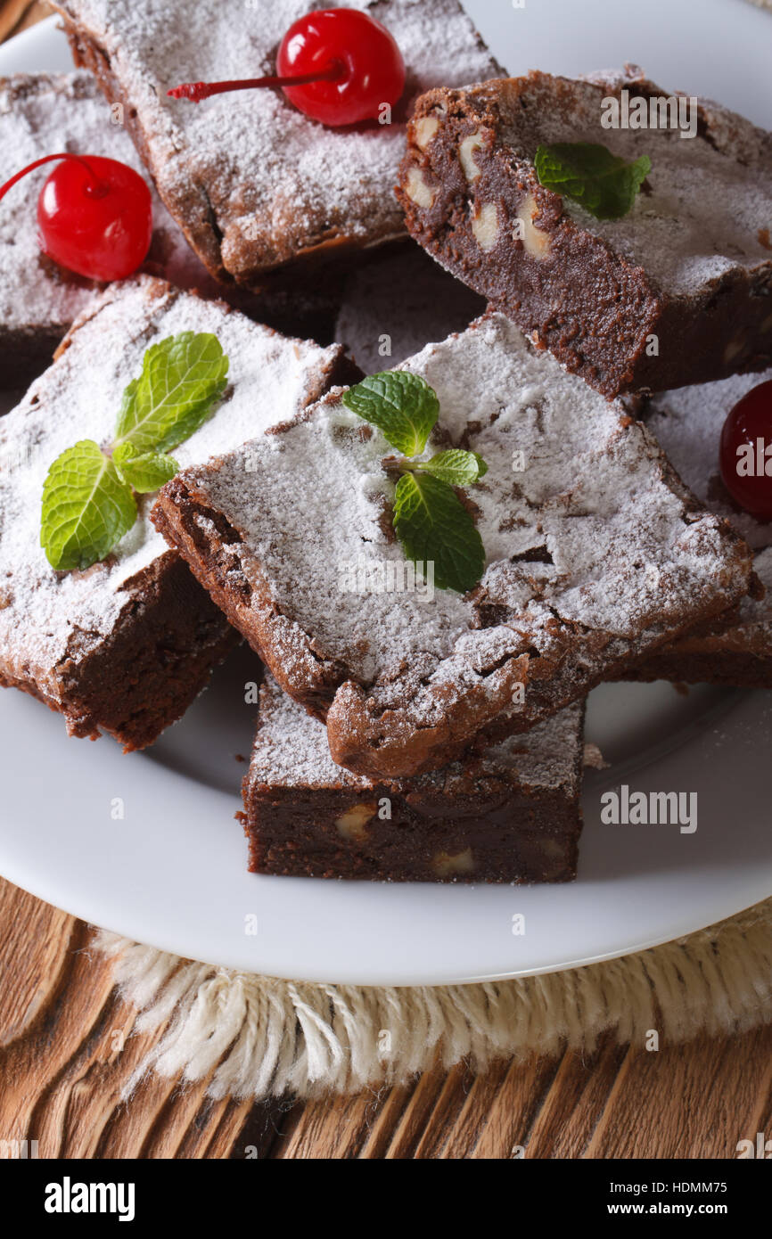 chocolate cake brownie with walnuts and cherries close-up. Vertical - Stock Image