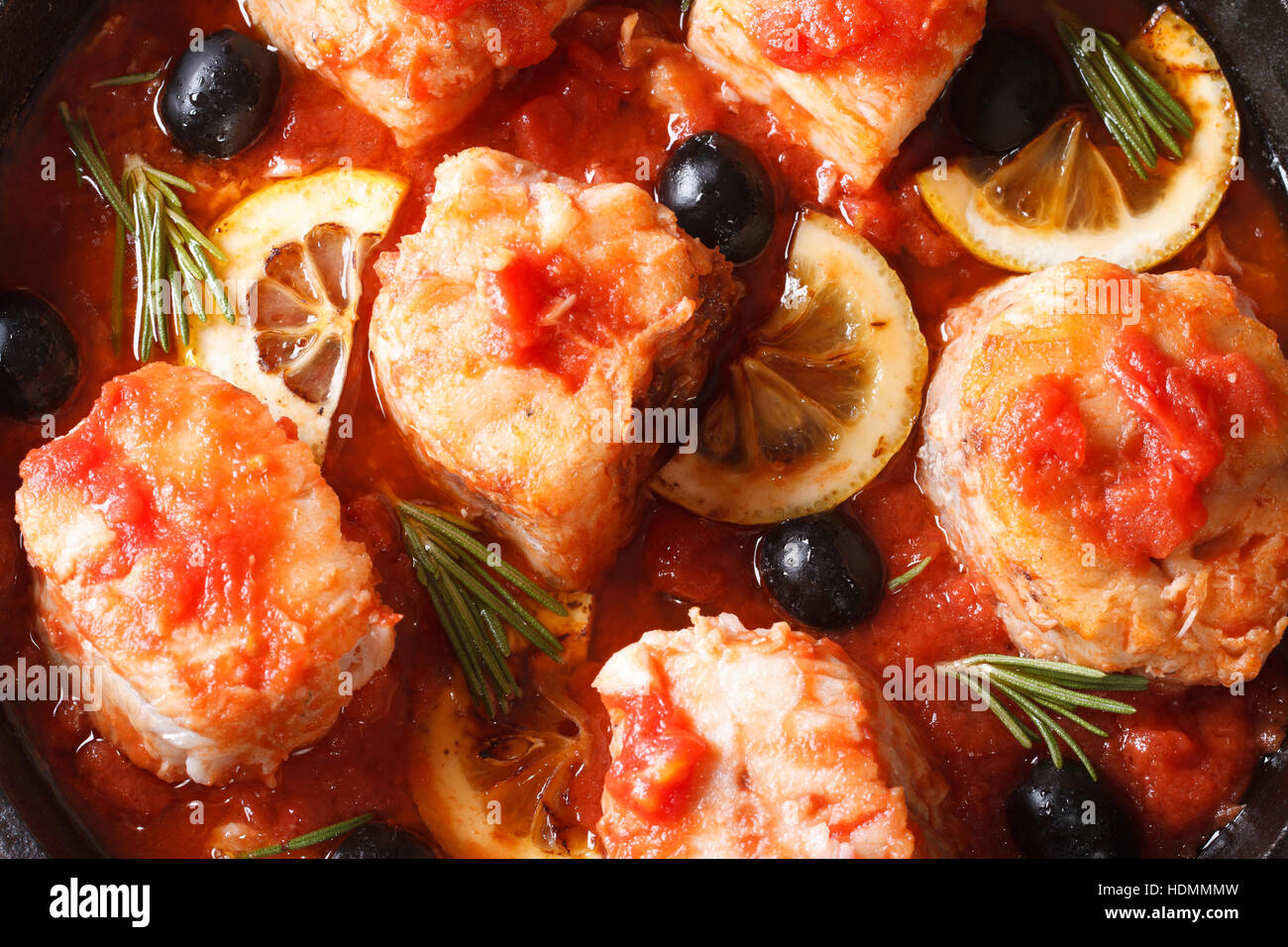 Fish fillet in tomato sauce with lemon and olives macro. horizontal view from above - Stock Image