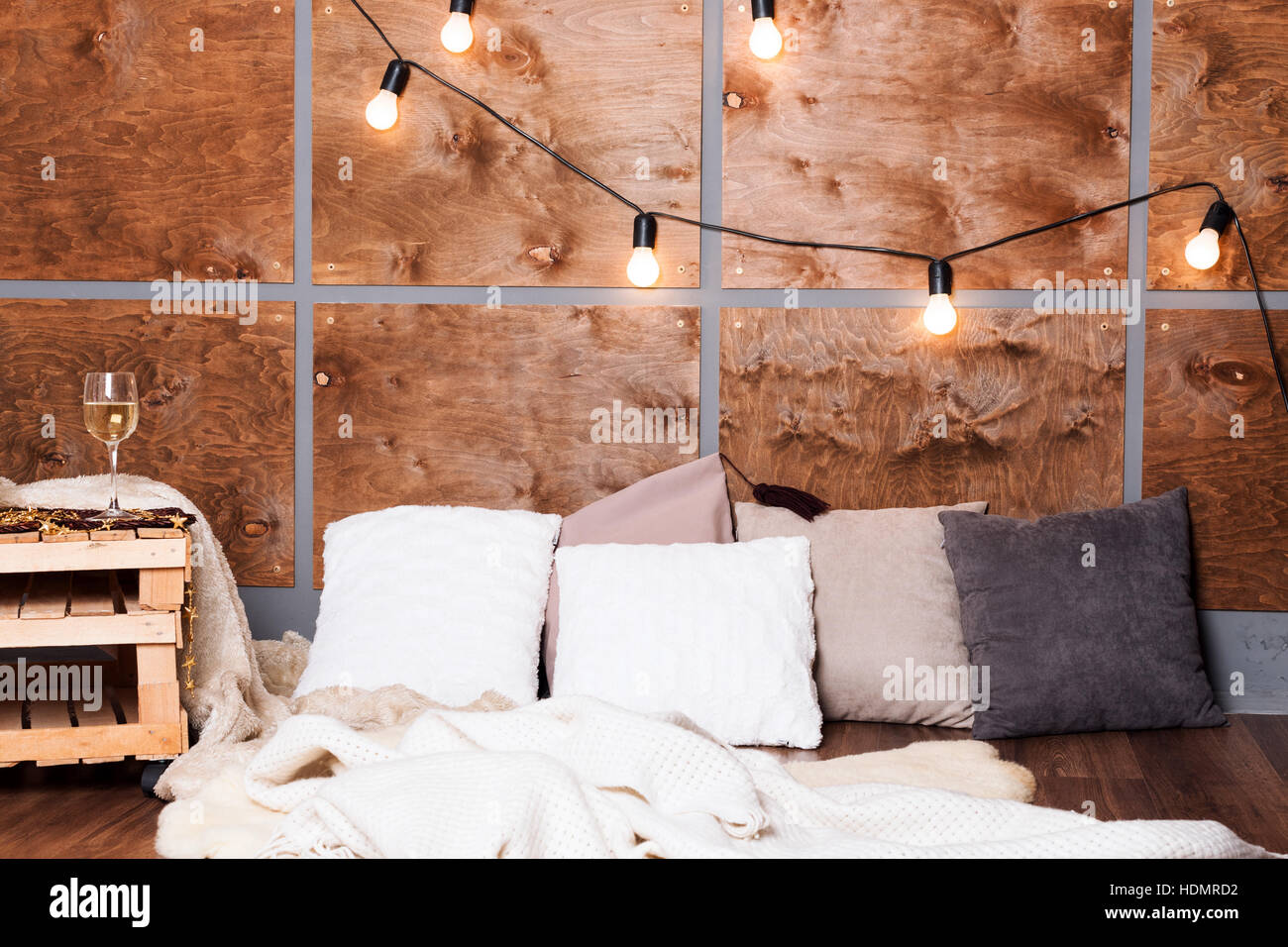 Glass of white wine in modern loft interior with light garland on wooden wall. Stock Photo