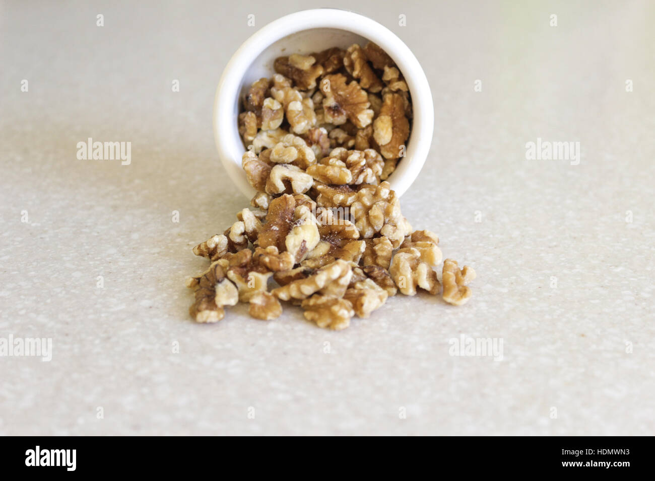 Delicious walnuts spilling out of a container on a kitchen countertop, ready to enjoy as a snack or in a favorite Stock Photo
