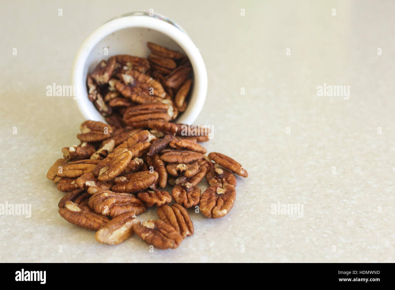 Delicious pecans spilling out of a container on a kitchen countertop, ready to enjoy as a snack or in a favorite - Stock Image
