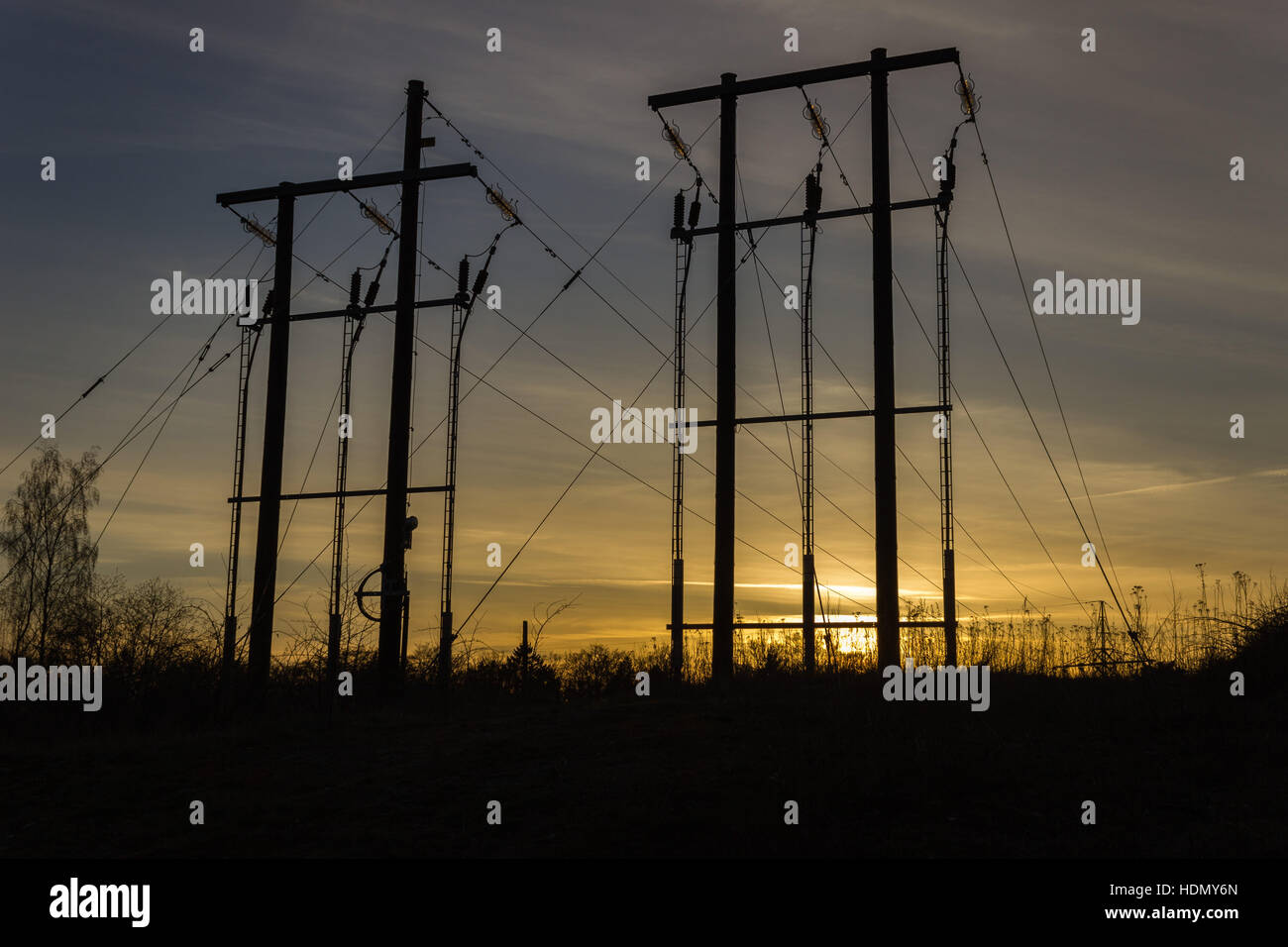 Silhouettes of power lines in a sunset scenario - Stock Image