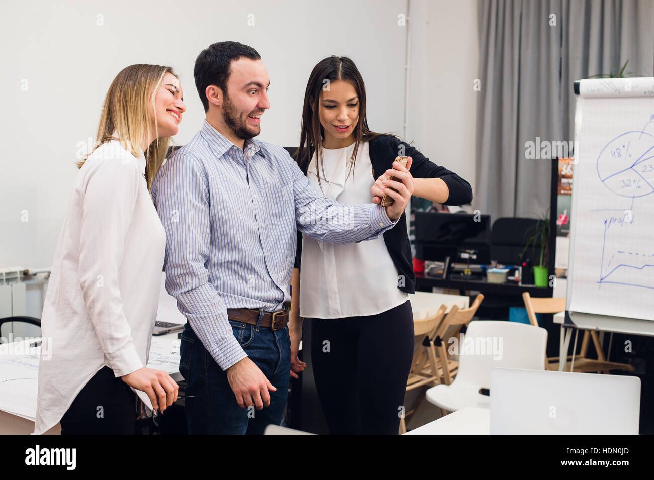Group of four diverse cheerful co-workers taking self portrait and making funny gestures with hands at small office Stock Photo