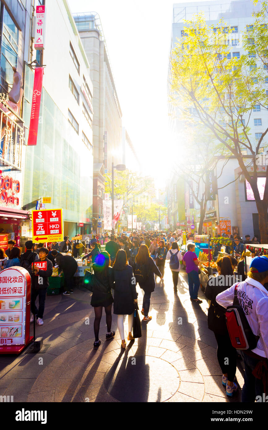 Tourists walking down busy backlit Myeongdong pedestrian shopping street with commercialism of stores, signs and - Stock Image