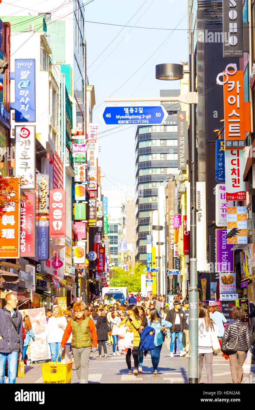 Tourists walking down bustling Myeongdong pedestrian shopping street surrounded by commercialism of stores, signs - Stock Image