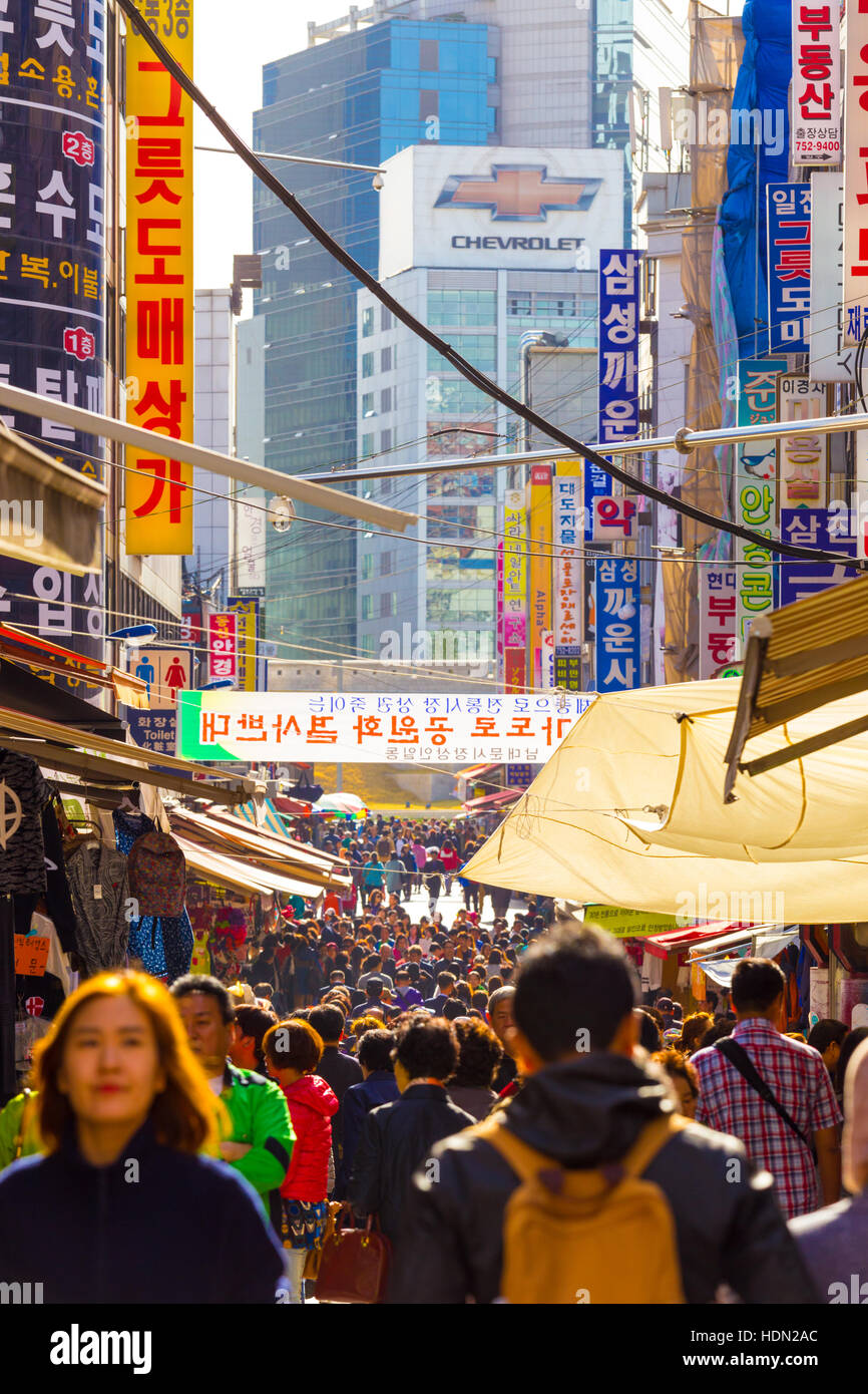 People walking down bustling Namdaemun Market pedestrian shopping street surrounded by stores, signs and crowded - Stock Image