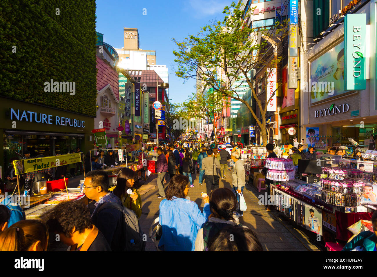 Tourists walking down narrow Myeongdong pedestrian shopping street with commercialism of stores, signs and crowded - Stock Image