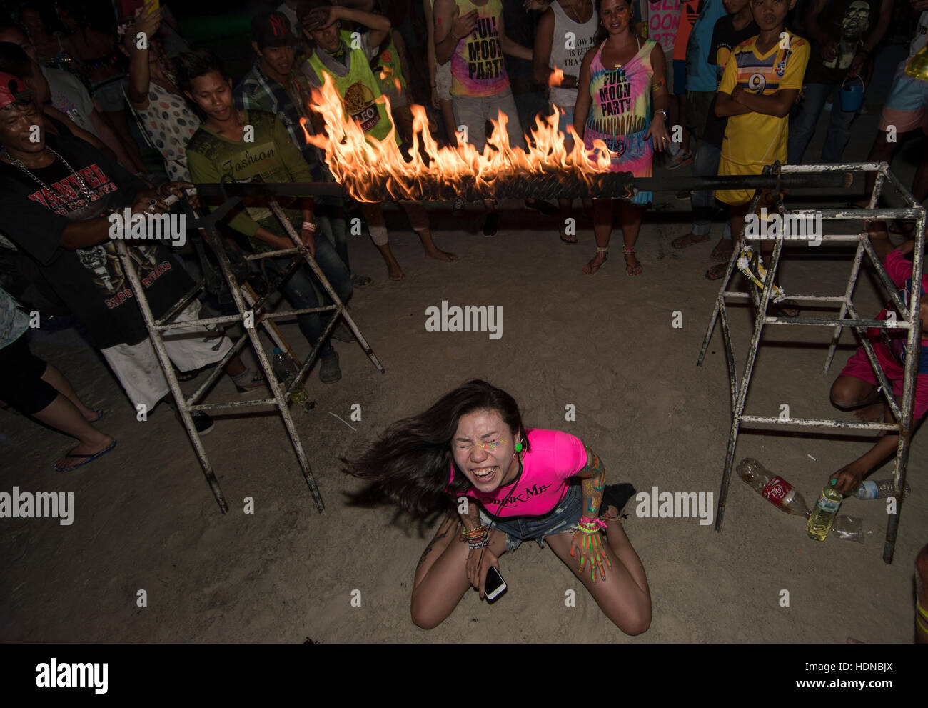 A party goer joins in a limbo dance under a burning pole at a  Full Moon party on Sunrise beach Haad Rin on the - Stock Image