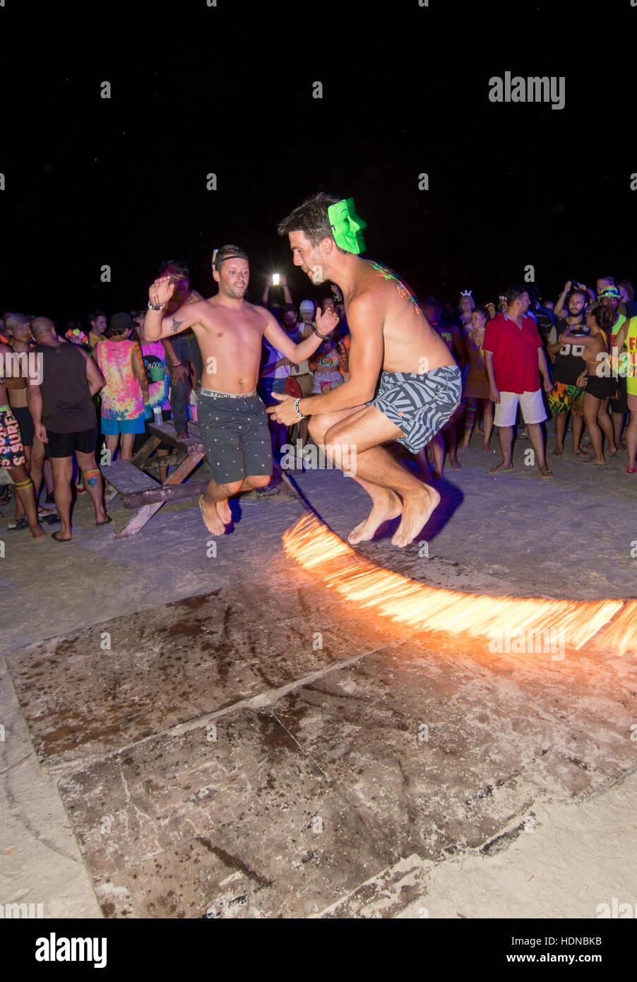 Party goers skip with burning rope at a Full Moon party on Sunrise beach Haad Rin on the island of Kho Phag Nang - Stock Image