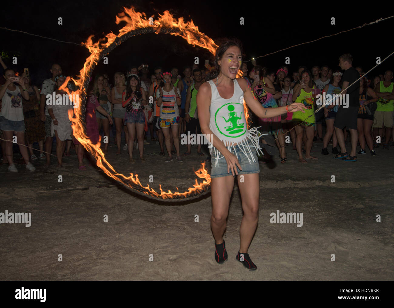 Female jumps through a burning hoop at a Full Moon party on Sunrise beach Haad Rin on the island of Kho Phag Nang - Stock Image