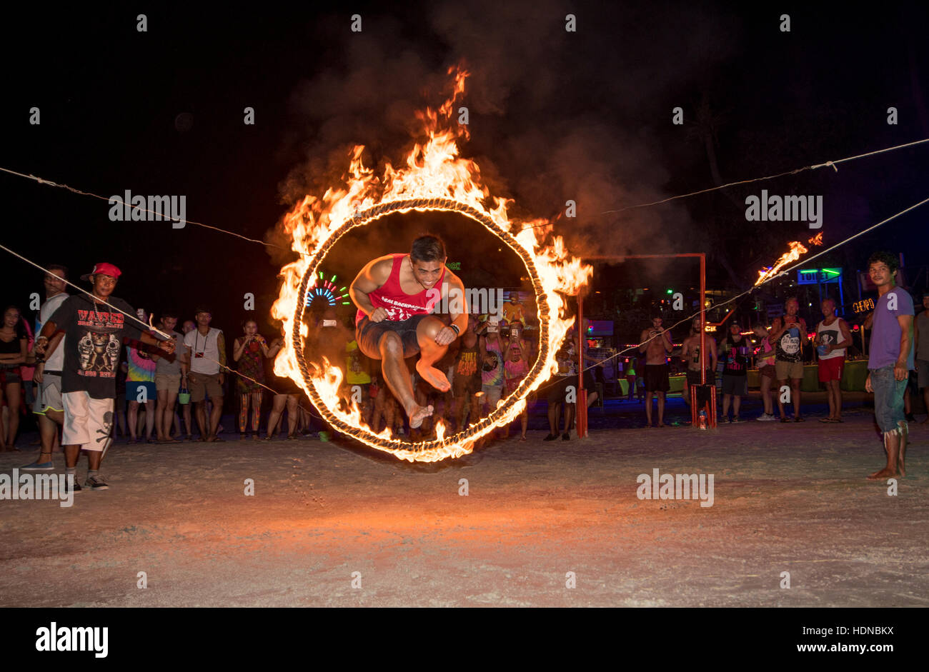 Male jumps through a burning hoop at a Full Moon party on Sunrise beach Haad Rin on the island of Kho Phag Nang - Stock Image