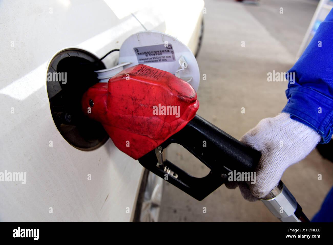 Shijiazhuang, Shijiazhuang, China. 14th Dec, 2016. A worker helps refuel a car at a gas station in Shijiazhuang, - Stock Image