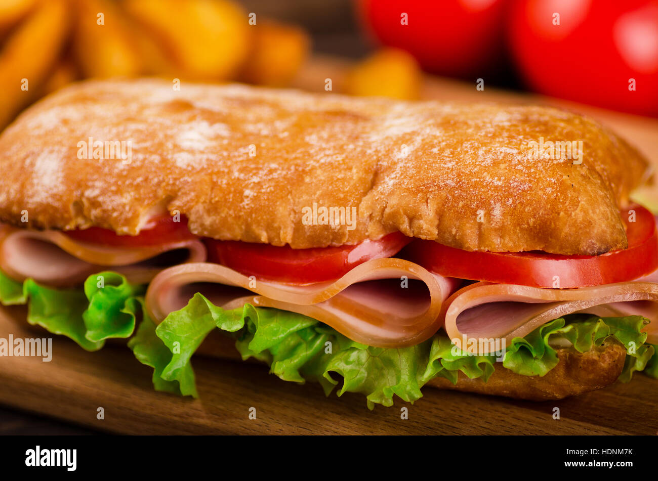 Long sandwiche with lettuce, slices of fresh tomatoes, ham - Stock Image