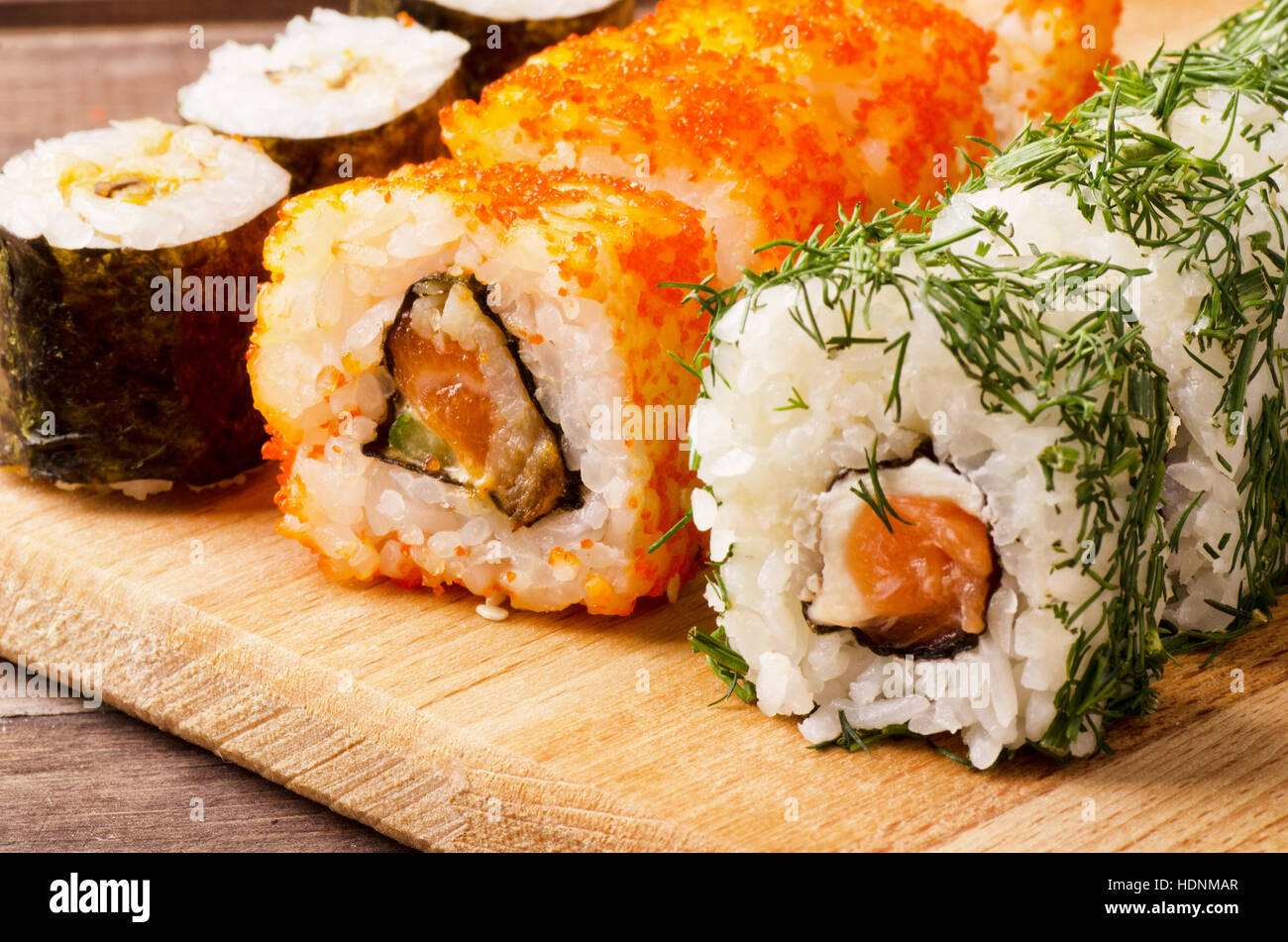 Japanese seafood sushi roll set on a cutting board - Stock Image