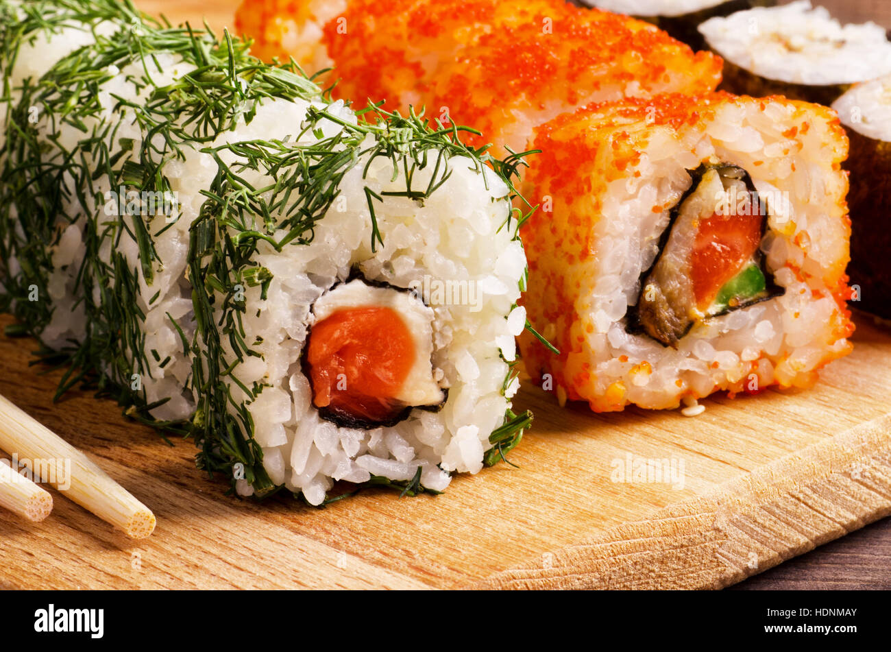 Japanese food, salmon sushi rolls set on a kitchen table with chopsticks - Stock Image