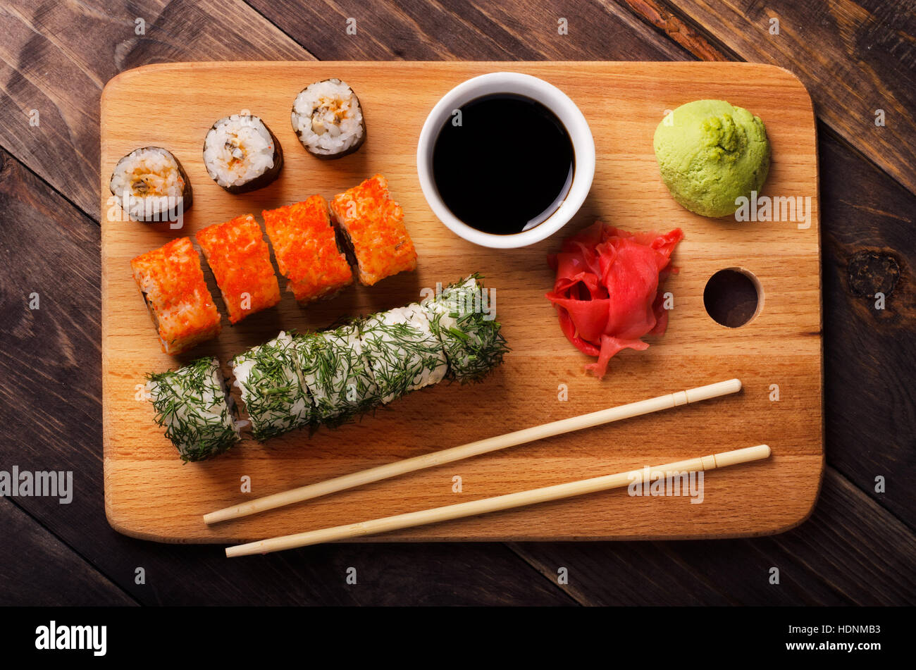 Sushi rolls with soy sauce, ginger and wasabi on cutting board close-up - Stock Image