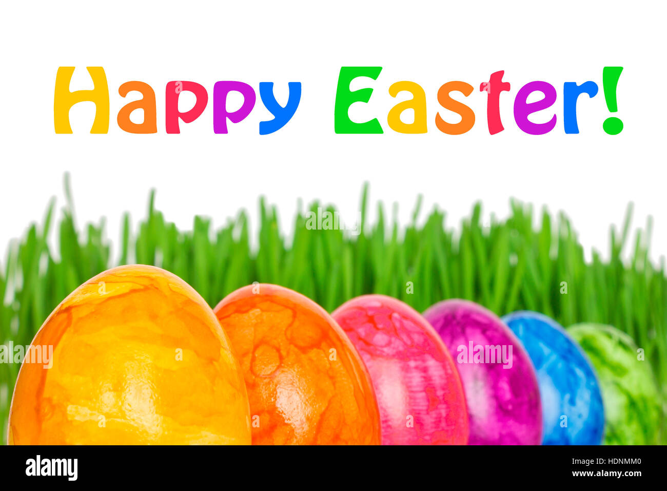 Row of 6 colorful Easter Eggs in front of green grass, text Happy Easter, in vivid rainbow colors - Stock Image