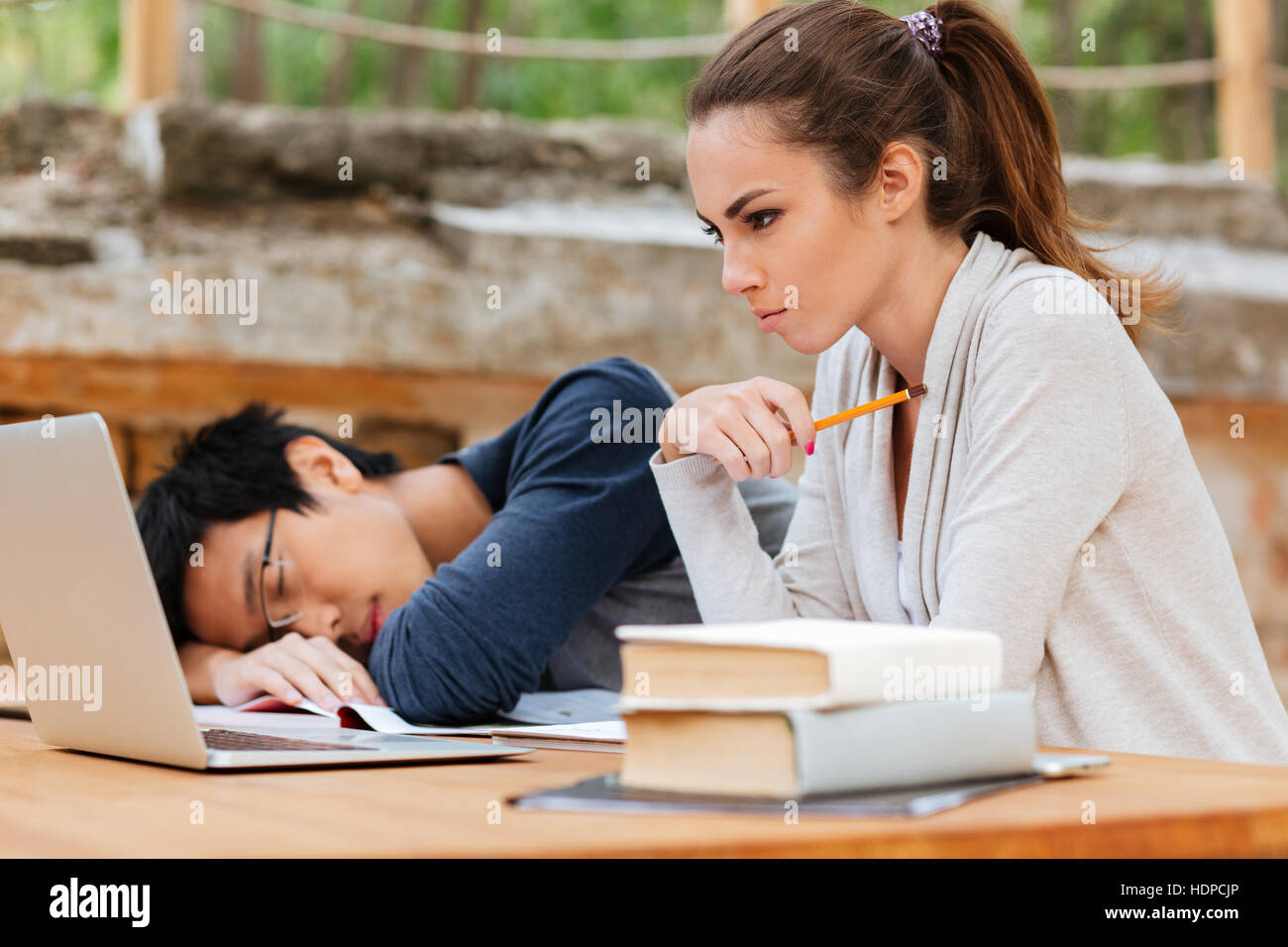 Concentrated young woman sitting and studying near man sleeping on the desk - Stock Image