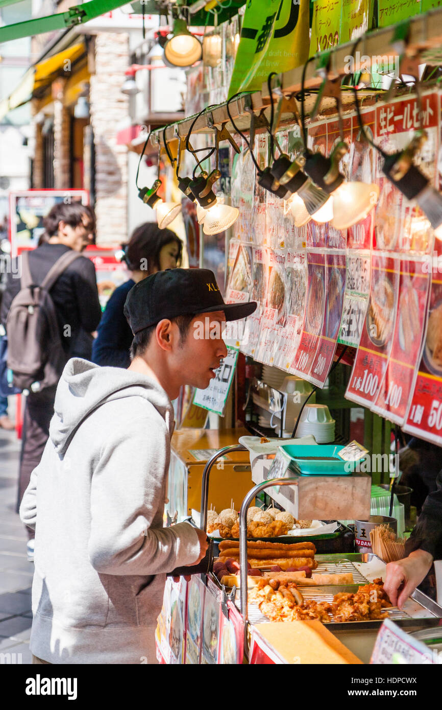 Japan, Kobe, Nankinmachi, Chinatown. Young Japanese man with baseball cap, ordering food from counter of Chinese - Stock Image