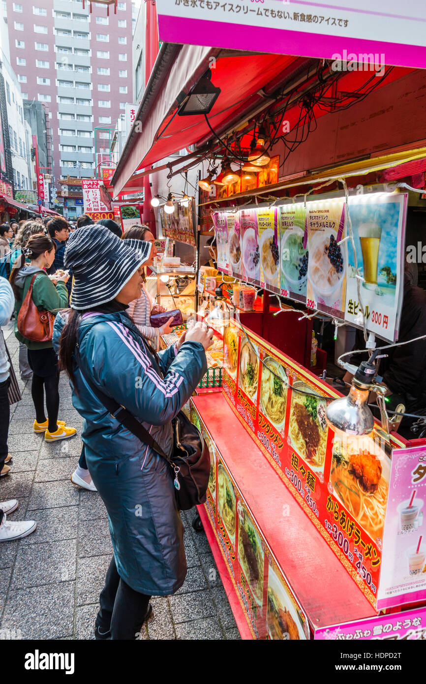 Japan, Kobe, Nankinmachi, Chinatown. Woman buying from outside Chinese food take-away counter in busy narrow road. - Stock Image