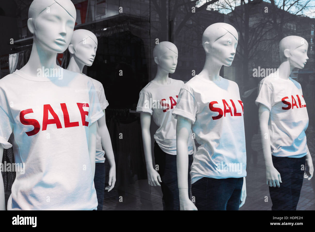 Window Display With Five Mannequins Wearing T Shirts With Text