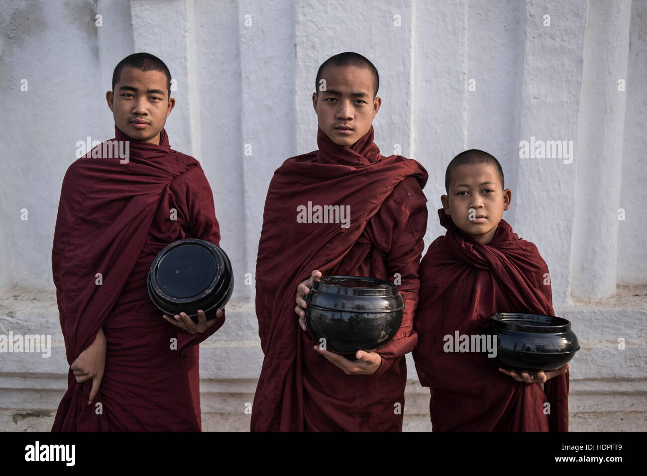 Three young Buddhist monks prepared to go the morning food alms collection,  Shwe Yan Pyay Monastery, Nyaungshwe, - Stock Image