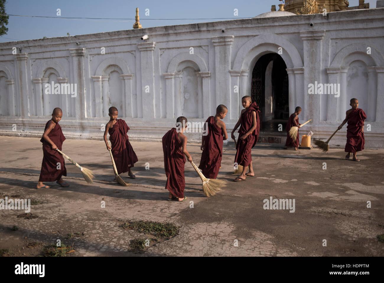 Young novice Buddhist monks sweeping around the grounds of the Shwe Yan Pyay Monastery in Nyaungshwe, Myanmar. - Stock Image