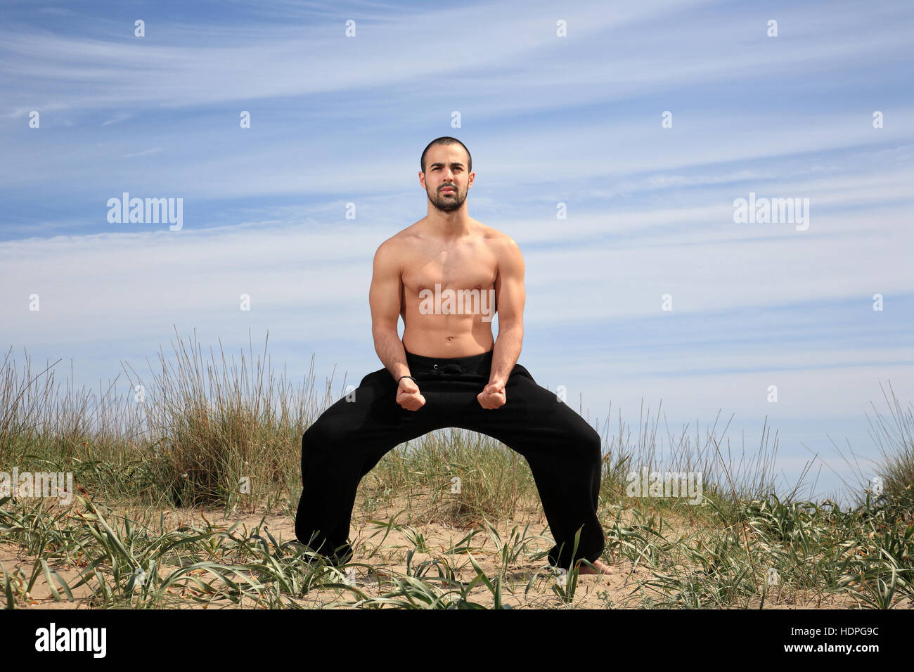 young male fighter exercising on a sand hill Stock Photo