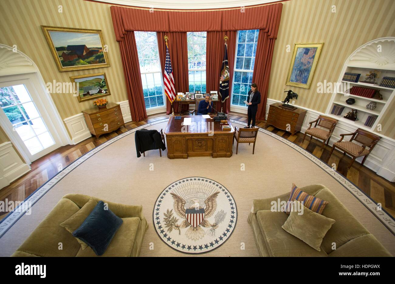 U.S. President Barack Obama talks on the phone on Thanksgiving Day at the White House Oval Office November 24, 2016 Stock Photo