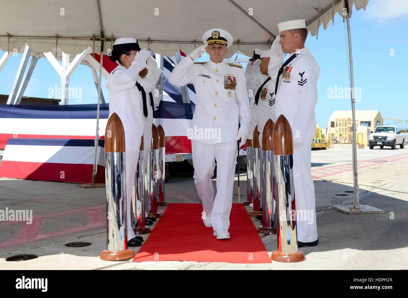 U.S. sailors salute U.S. Pacific Fleet Submarine Force commander Phillip Sawyer as her arrives at the change-of - Stock Image