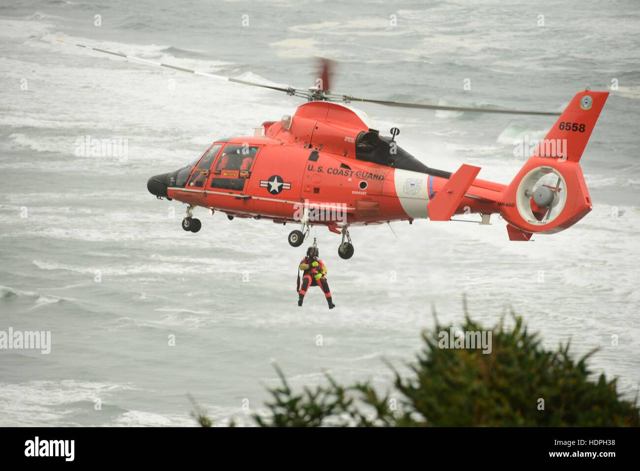 A U.S. Coast Guard pararescue officer is lowered from a Eurocopter MH-65 Dolphin search and rescue helicopter during - Stock Image