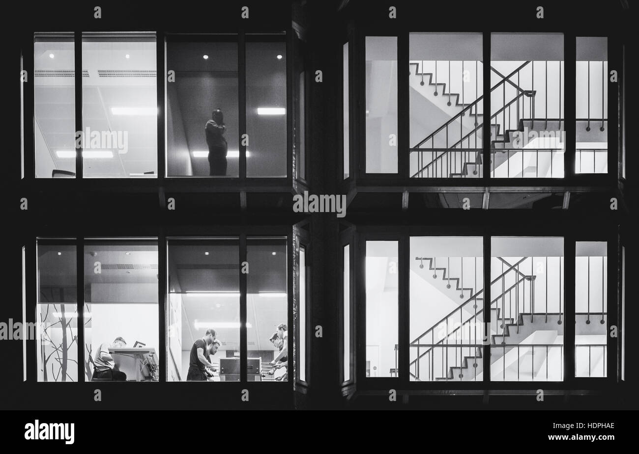 Image depicting various scenes from within an office shot from outside. - Stock Image