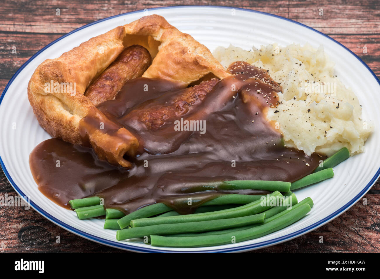 Classic British dinner of Toad in the Hole with thick gravy. - Stock Image