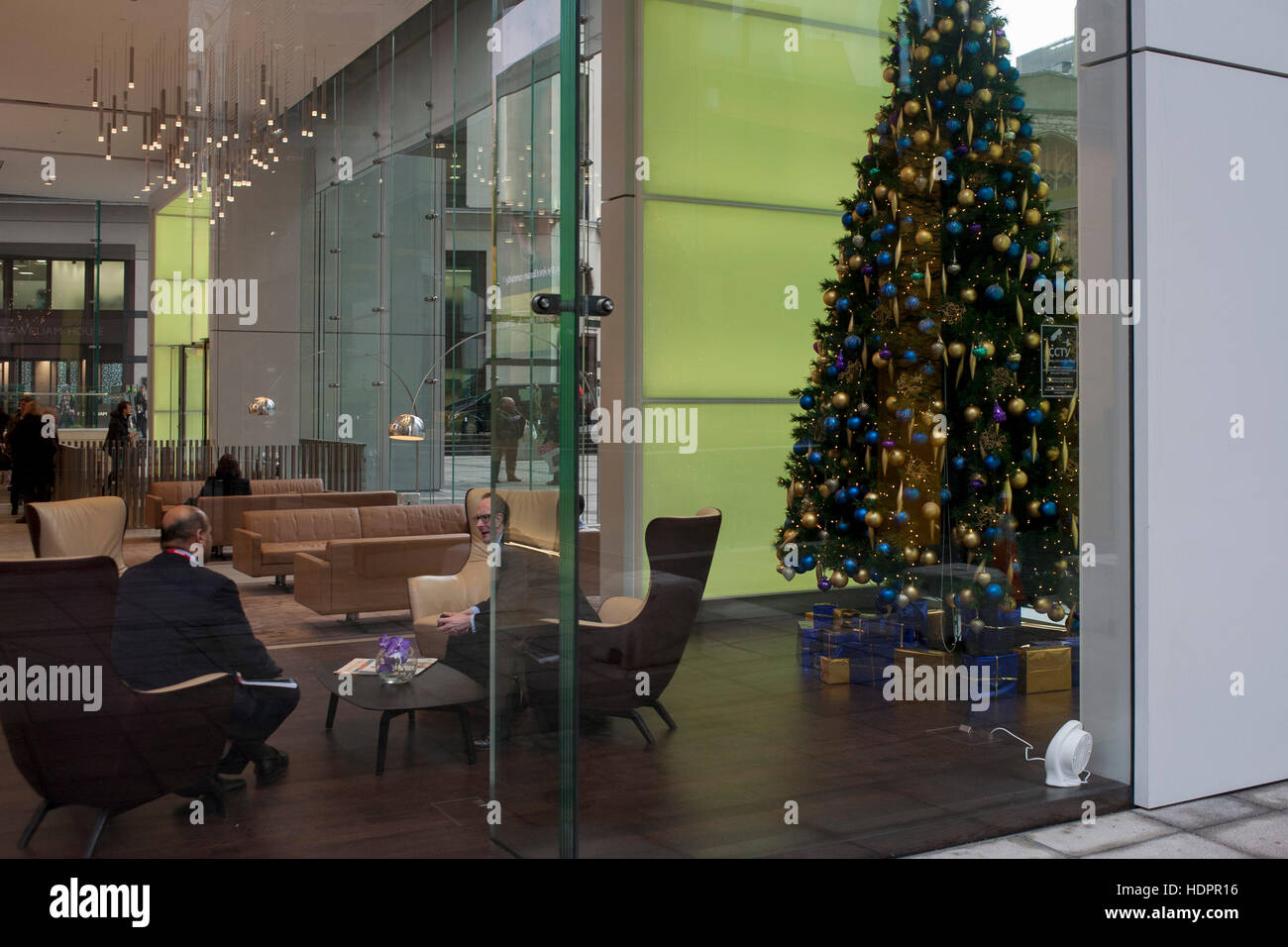 Businessmen meet in the Aviva office foyer in front of a Christmas tree at the insurance corporate's HQ, on - Stock Image