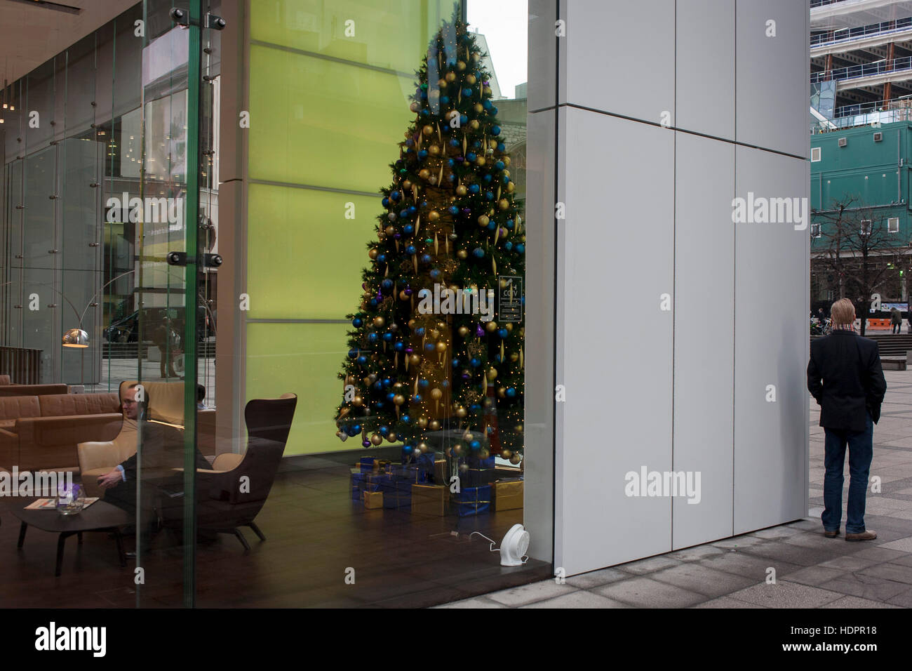 A distorted businessman and a bystander at the Aviva office foyer in front of a Christmas tree at the insurance - Stock Image