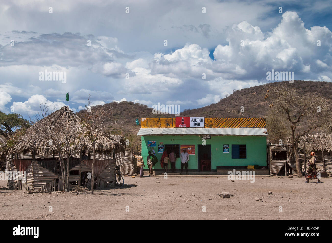People standing outside a building with grocery and bar, Mangola, Lake Eyasi, Manyara region, Tanzania - Stock Image