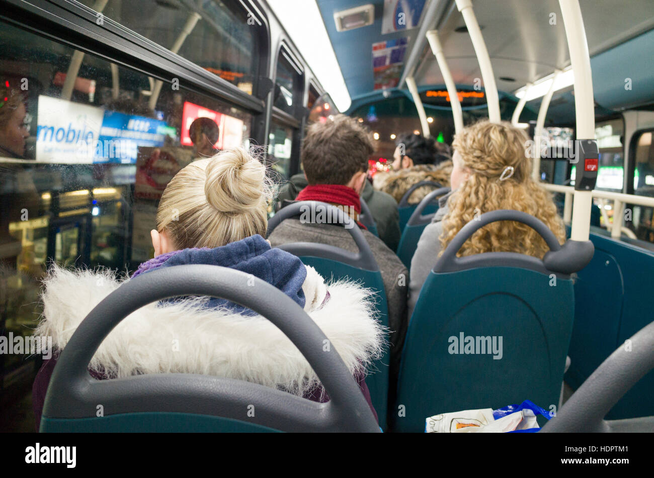Bus passengers on the top deck of a night bus, London, England, UK - Stock Image